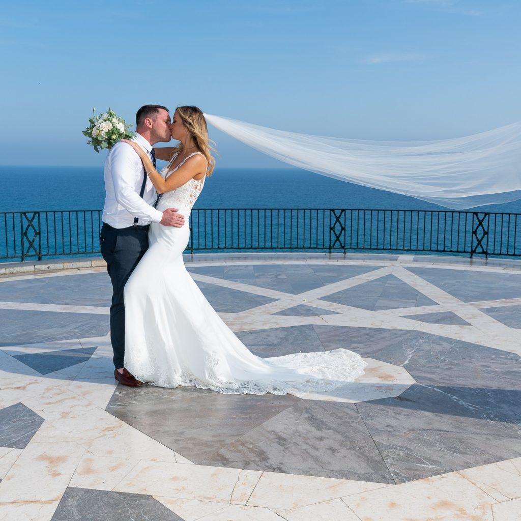 Newlyweds bride and groom kiss Balcon de Europa Nerja Spain